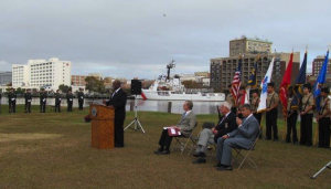 New Hanover County Commissioners Chairman Jonathan Barfield addresses annual Pearl Harbor commemoration at Battleship Park. American Legion Post 10 Honor Guard, USCGC Diligence, and Ashley High School Navy JROTC are backdrop. Seated Wilbur Jones, COL Robert Newman, USAF (Ret.) and Mayor Bill Saffo.